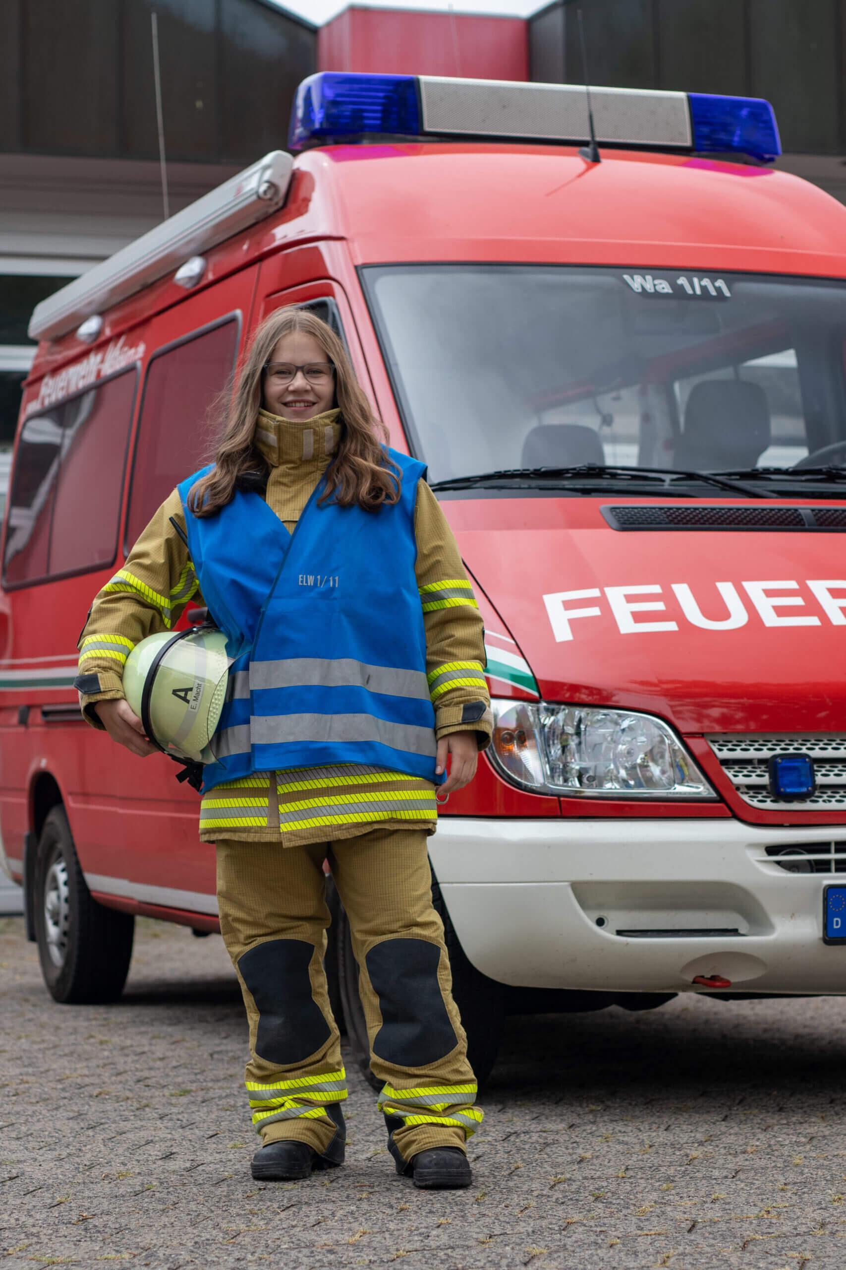 Feuerwehrfrau mit einer blauen Funktionswesten vor dem Einsatzleitwagen.